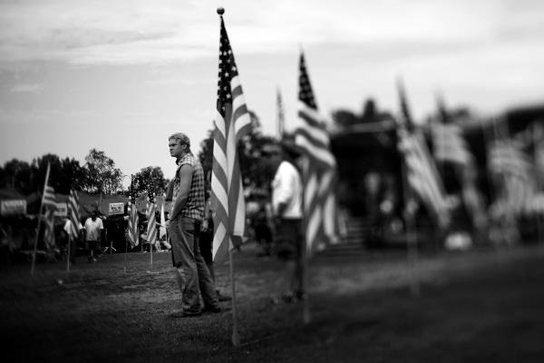 Veterans stand in the center of the grounds, surrounded by American flags.