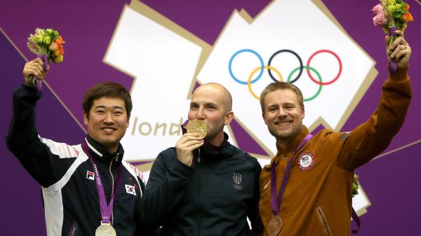 Matthew Emmons of America (right) celebrates his bronze medal, along with Italy's Niccolo Campriani (center) and South Korea's Kim Jonghyun, after the men's 50m rifle 3 positions final.