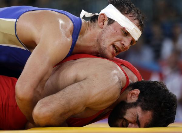 Alan Khugaev of Russia (in blue) competes against Vladimer Gegeshidze of Georgia during the 84kg Greco-Roman wrestling semifinal. Khugaev went on to win gold in the final.