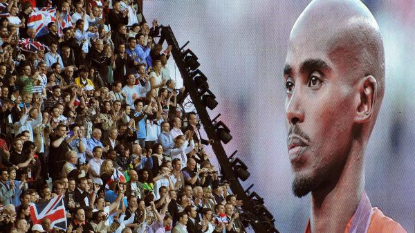 British runner Mo Farah is cheered as he appears on a giant screen at Olympic Stadium, accepting his gold medal for the 10,000 meters. Farah has become a celebrity in Britain since his win.