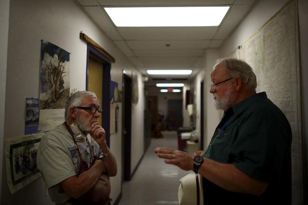 Adams (left) talks with Swetnam in their laboratory, nestled under the football stadium.