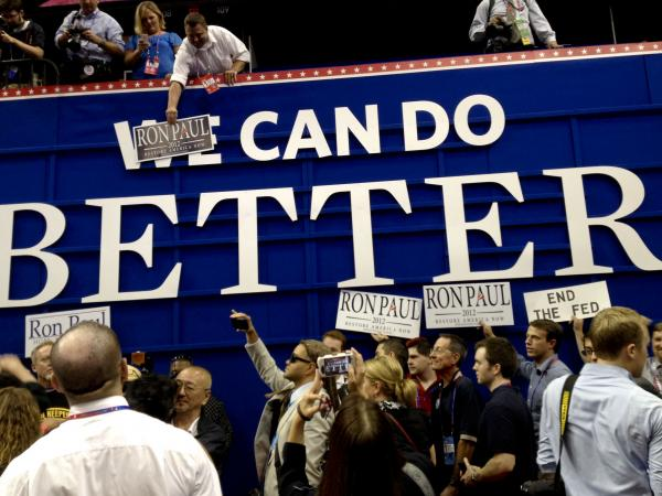 "Ron Paul supporters pose with posters on the floor of the RNC on Monday in Tampa. They put ""Ron Paul"" over the word ""We"" on a GOP sign that says ""We Can Do Better."""