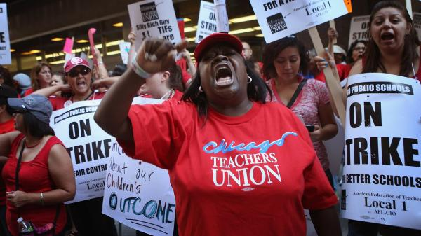 Chicago public school teachers and their supporters picket in front of the Chicago Public Schools headquarters.
