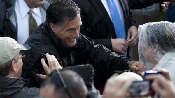 Republican presidential candidate Mitt Romney shakes hands during a rainy campaign rally Monday in Newport News, Va.