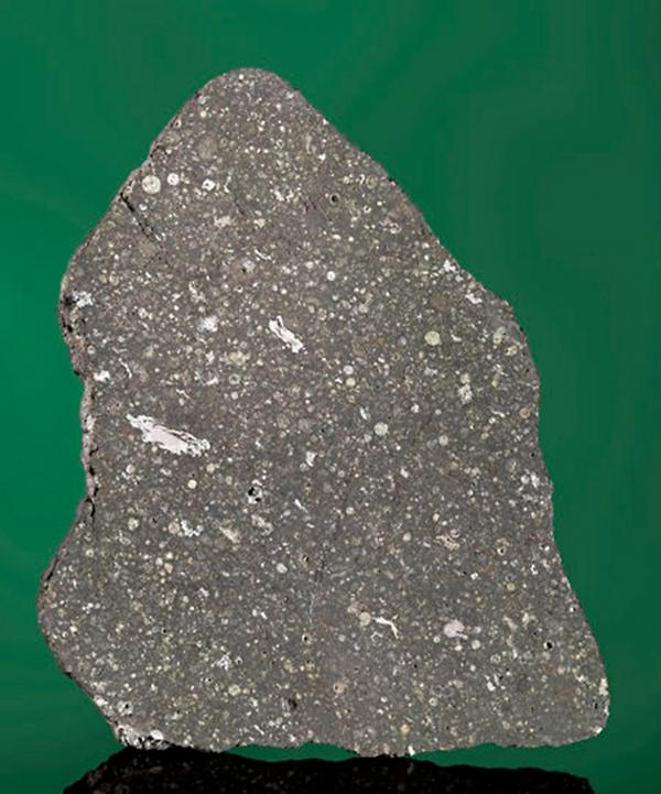 <strong>Touch Stardust:</strong> A slice of the Allende meteorite that fell in Chihuahua, Mexico, in 1969. It contains white calcium-aluminum inclusions, material present at the birth of our solar system.