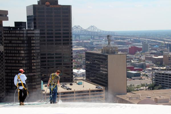 "Rene Lopez and Devin Burrell blast dirt off the polyurethane coating the iconic white roof of the Superdome in New Orleans. The job will cost about $130,000 and take roughly a month, partly because the roofers must move slowly. ""You have to constantly be aware of where you're at,"" says project manager Tom Keller. ""If something stupid happens, it's not going to end up pretty."""