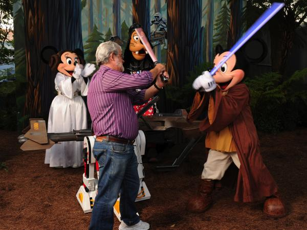In this handout image provided by Disney, Star Wars creator George Lucas has a playful lightsaber duel with Jedi Mickey Mouse at Disney's Hollywood Studios theme park at Walt Disney World Resort in Lake Buena Vista, Fla., on Aug. 14, 2010. Disney announced Tuesday that it was buying Lucasfilm Ltd. for $4.05 billion.