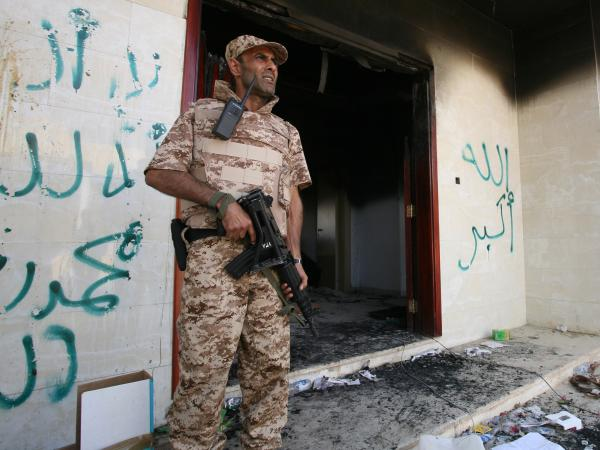 A Libyan military guard stands in front of one of the U.S. Consulate's burned out buildings on Sept. 14. The U.S. is offering new details of the attack on the consulate that killed four Americans, including Ambassador Chris Stevens.