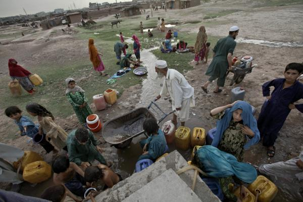 Afghan refugees collect water from a water point in a slum area on the outskirts of Islamabad, in May.