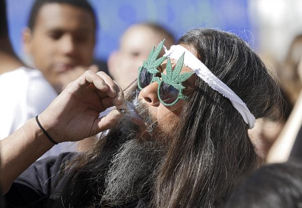 Fast Eddy Aki'a of Hawaii smokes a joint as thousands of supporters of legalized pot, lit up at 4:20 p.m. on April 20 in Denver, Colorado.