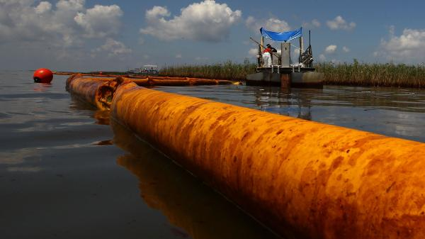 June 2010: A boom floats in the water as contract workers from BP use skimmers to clean oil from a marsh near Venice, La.