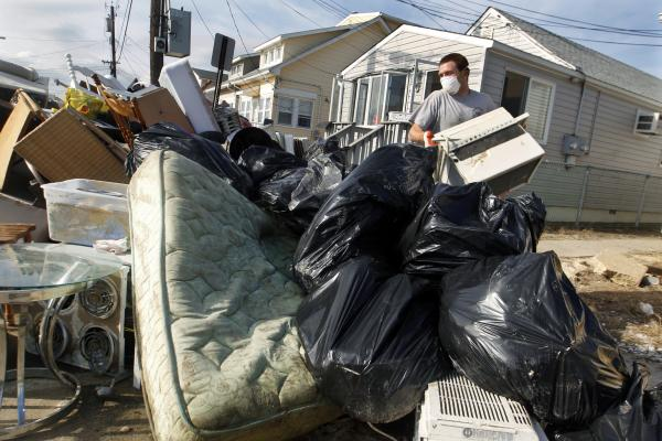Ernest Shallo, of Carteret, N.J., throws a ruined air conditioner onto a pile of debris in front of a small home in Seaside Heights, N.J. Residents were allowed back in their homes for a few hours Monday, two weeks after the region was pounded by Superstorm Sandy.