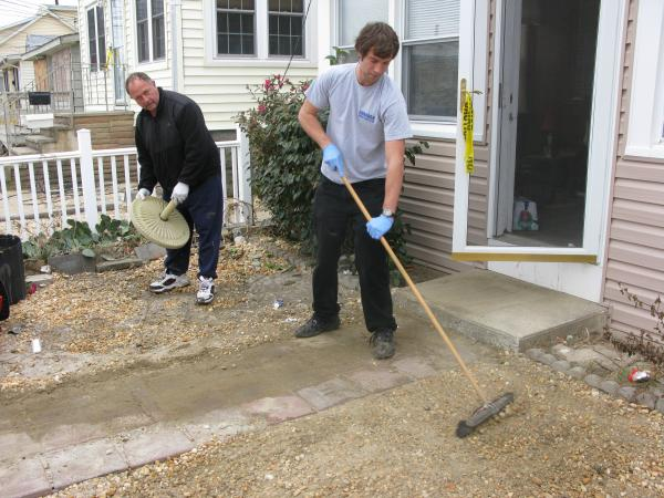 Wayne Duszczak (left) and his son Anthony clean up the gravel yard of their Seaside Heights home, which was badly damaged during Superstorm Sandy.