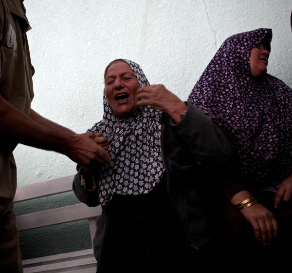 Palestinians react after they checked the body of their family member killed in an Israeli air strike, at Al-Adwan Hospital in Gaza City on Tuesday.