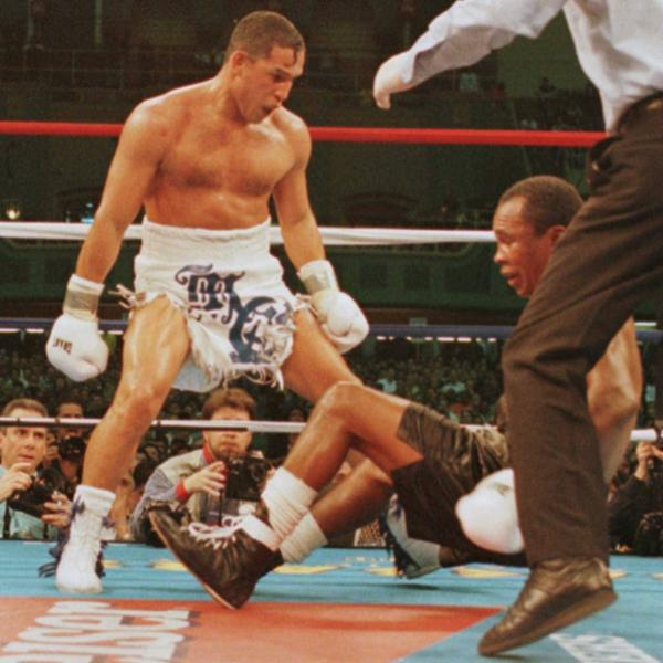 "March 1, 1997: Hector ""Macho"" Camacho watches as ""Sugar"" Ray Leonard falls to the canvas during action in the fifth round of their fight."