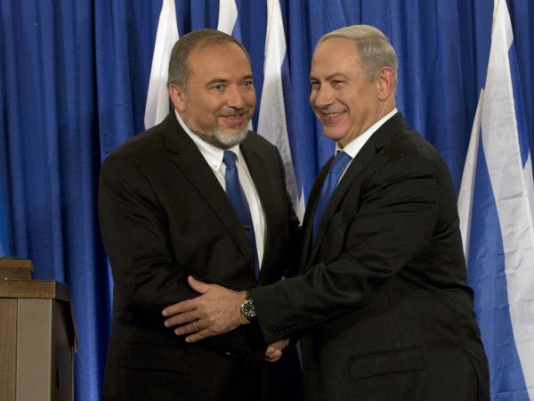 Israeli Prime Minister Benjamin Netanyahu (right) and Foreign Minister Avigdor Lieberman shake hands in front of the media after giving a statement in Jerusalem last month. Netanyahu said his Likud Party will join forces with the hard-line party of his foreign minister in upcoming parliamentary elections.