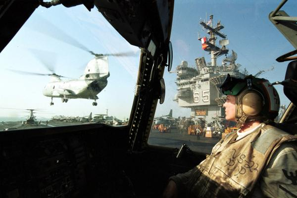 A Navy aviation machinist on the Enterprise watches a Ch-46 Sea Knight fly by after delivering supplies, Oct. 10, 2001. The ship and its carrier battle group were conducting flight operations in Afghanistan following the Sept. 11 attacks.
