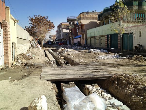One of the streets undergoing renovation in Kabul. Residents often have to build makeshift bridges at their own expense to span the sewage trenches and reach their garages or driveways.