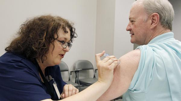 Bill Staples, a Mississippi health department worker, gets a flu shot in October. Mississippi is one of eight states where flu is already widespread this season.