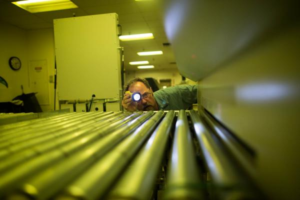 Bradley McComb, a production and maintenance mechanic, inspects a machine that makes metal plates for the presses.