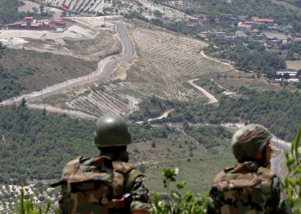 In this June 2011 photo, Syrian soldiers look down on the village of Khirbet al-Joz, on the border with Turkey. Syrian rebels recently captured the village, and residents are setting up a secular, democratic leadership they hope will serve as a model.