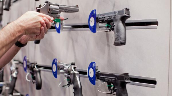 A visitor handles a revolver at a Smith & Wesson display during the NRA Annual Meetings and Exhibits on April 14 at America's Center in St. Louis, Mo.