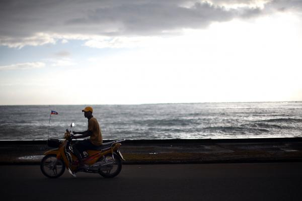 A motorcyclist rides along the main promenade in Cap-Haitien next to the harbor and the bay. Haiti has miles of undeveloped beaches and coastline that tourism officials say should be used to attract foreign investment.