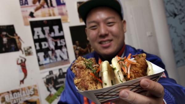 "Eddie Huang, co-owner of Baohaus and author of <em>Fresh Off The Boat</em>, holds a pair of ""The Taiwanese Te-Bao,"" a Taiwanese pork chop with curry seasoning, pickles daikon-carrot, jalapeno, aioli and cilantro in a steamed bun."