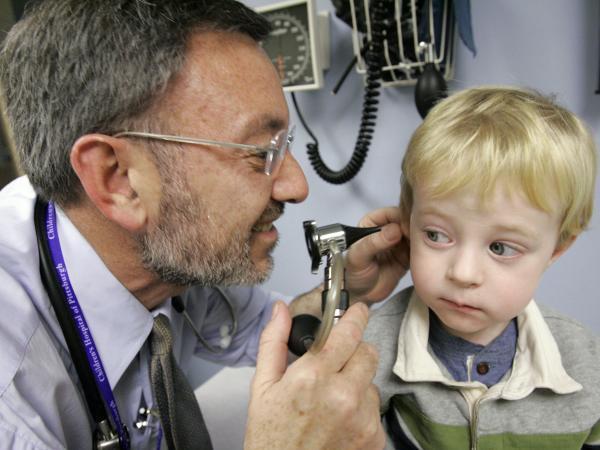 Giancario Gemignani-Hernandez, 2, of Pittsburgh has his ear examined by Dr. Alejandro Hoberman.