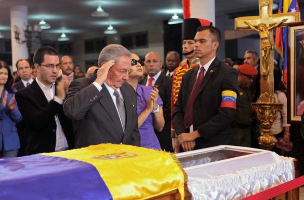 In this photo released by Miraflores Press Office, Cuba's President Raul Castro salutes as he stands next to the coffin containing the body of Venezuela's late President Hugo Chavez.