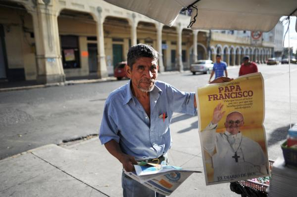 A man in San Salvador sells a newspaper with the announcement of the election of Argentina's cardinal Jorge Mario Bergoglio as the new Pope Francis.