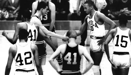 Mississippi State's team captain, Joe Dan Gold (back left), and Loyola All-American Jerry Harkness (back right) meet at center court for the tipoff in the 1963 NCAA basketball tournament.