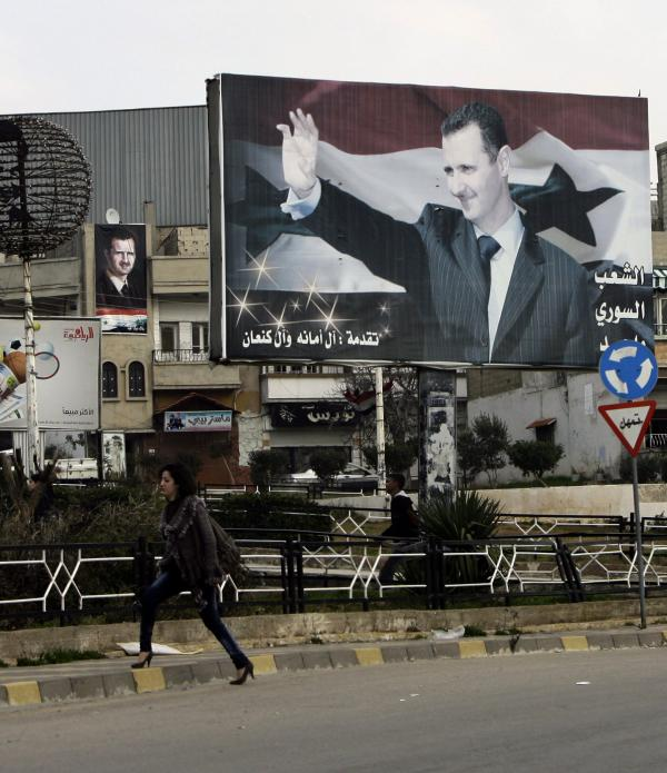 A Syrian woman walks past a poster for President Bashar Assad in an Alawite-dominated neighborhood in the western city of Homs, on Jan. 11, 2012. Support among the president's own minority sect is waning.