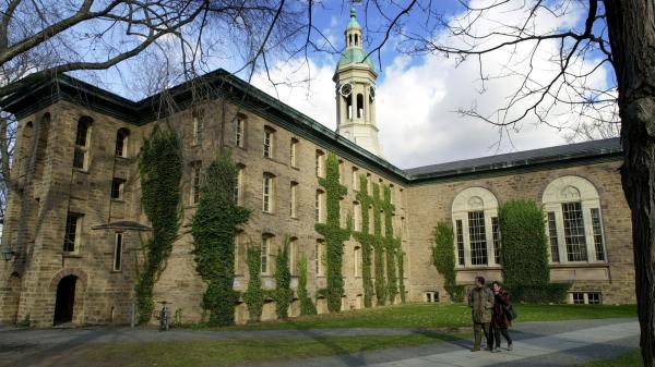 A couple walks past Nassau Hall on the Princeton Unversity campus in Princeton, N.J. A letter to the editor in <em>The Daily Princetonian</em> urging female students to find a husband before they graduate has drawn criticism.