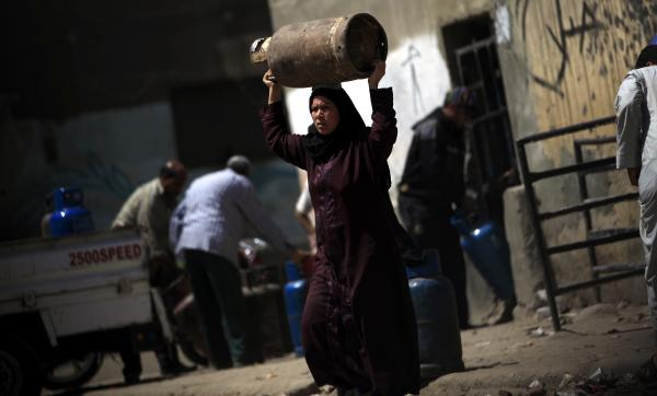 An Egyptian woman carries a cooking gas canister in Cairo on Tuesday. The government just raised the price of gas as part of an energy package needed to satisfy the conditions of a $4.8 billion IMF loan. Opponents say some of the conditions disproportionately hurt the poor.