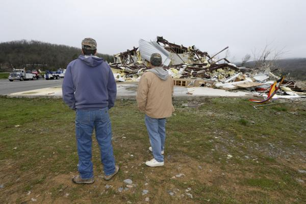 Larry Gammill, left, and Tim Parks survey tornado damage at a church in Botkinburg, Ark. on Thursday after the building was hit by a tornado. Three tornadoes touched down in Arkansas on Wednesday. The National Weather Service is warning more storms are on the horizon as another warm, wet front is moving up from the Gulf of Mexico.