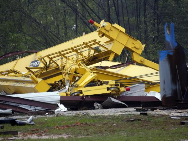 Heavy cranes are covered by debris after a tornado ripped through Kemper County, Miss., on Thursday. A man who was working at the site was killed and another was injured. The tornado was one of at least 12 that touched down in states from Missouri to Georgia this week.