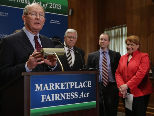 Sen. Lamar Alexander, R-Tenn. (left), leads a news conference about the Marketplace Fairness Act on Tuesday. The legislation would provide states with the authority to require out-of-state retailers to collect and remit taxes on purchases shipped into the states.