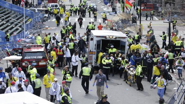 First responders aid injured people at the finish line of the Boston Marathon after the bombing on April 15.