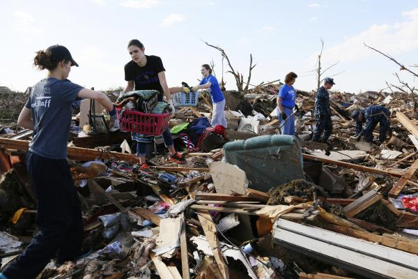 Volunteers form a chain as they retrieve clothing and other household items Wednesday at a home destroyed by a tornado, across the street from Plaza Towers Elementary School in Moore, Okla.