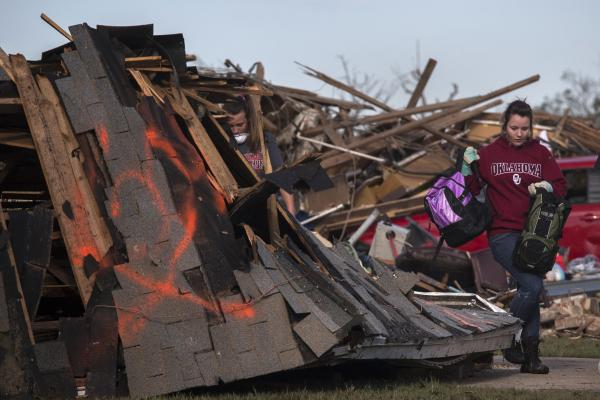 A resident walks past a fallen roof after salvaging belongings from her home in Moore. The National Weather Service said Monday's tornado produced winds in excess of 200 mph, making it a top-of-the-scale EF5.