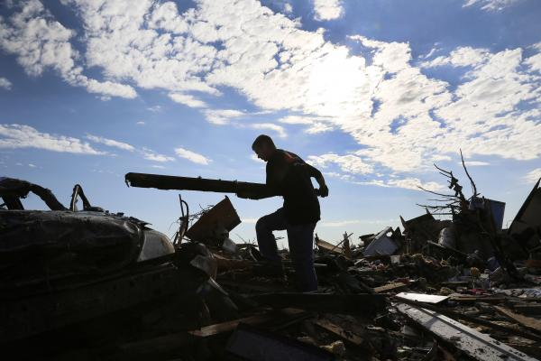 Jon Booth carries debris from his mother's tornado-destroyed home across the street from Plaza Towers Elementary School in Moore.
