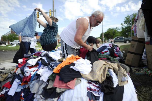 Tornado victim Todd (who only gave one name) looks through a pile of clothing at a roadside relief camp in Moore. The twister flattened block after block of homes as it struck at midafternoon Monday, hurling cars through the air, downing power lines and setting off localized fires in a 45-minute rampage.