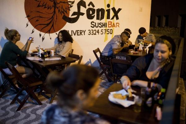 Members of the Pacification Police dine with local residents at the Fenix Sushi Bar in the <em>favela</em> Vidigal. The sushi bar is just one of several new businesses that attract people to the <em>favela</em>.