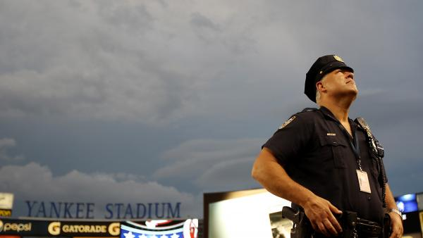 As the sky darkened and the storm moved in Sunday at Yankee Stadium, this police officer was among many warily looking up.