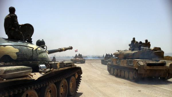 Syrian army tanks make their way toward a military airfield north of the city of Qusair on Sunday. Syrian forces have been battling opposition troops for control of the key city in recent weeks.
