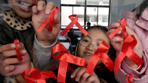 Students paste red ribbons on a window to mark World AIDS Day in Nanjing, China, in 2006. Although many infectious diseases have declined in the country, the number of new HIV cases nearly quadrupled between 2007 and 2011.