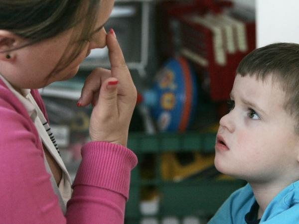 Instructional assistant Jessica Reeder touches her nose to get Jacob Day, 3, who has autism,  to focus his attention on her during a therapy session in April 2007.