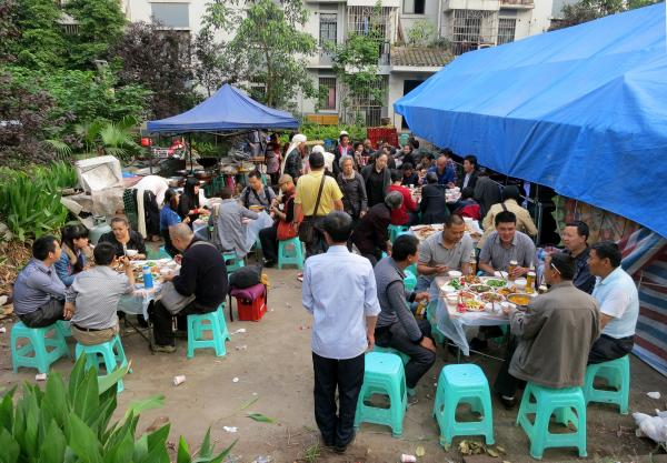 Dozens of friends and family of the deceased, Zhang Tujin, gather to feast on a big pre-funeral meal and celebrate his life. The meal takes place outside, in the shadow of a modern apartment block, and with skyscrapers going up in the distance. This funeral is a mix of ancient Chinese practices and modern entertainment.