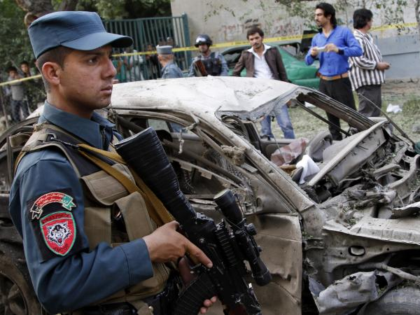 An Afghan policeman stands guard at the scene of a suicide car bomber attack that struck outside the Afghan Supreme Court in Kabul, on June 11.